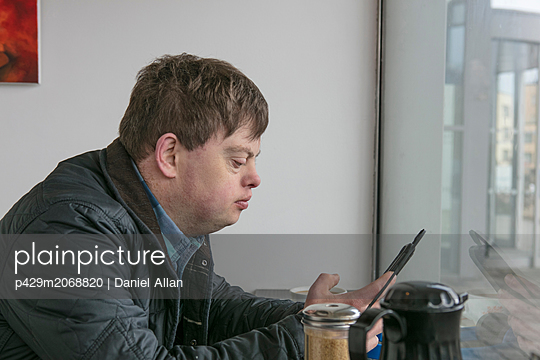 Man with down syndrome using phone by cafe window - p429m2068820 by Daniel Allan