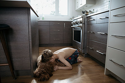 Affectionate bare chested boy cuddling dog laying on kitchen floor - p1192m1567278 by Hero Images