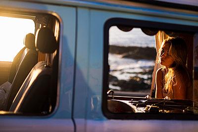 Spain, Tenerife, Blonde girl sitting in a  van at sunset - p300m1535632 by Simona Pilolla
