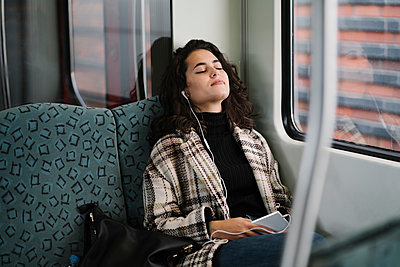 Young woman with closed eyes relaxing on a subway - p300m2143475 von Hernandez and Sorokina