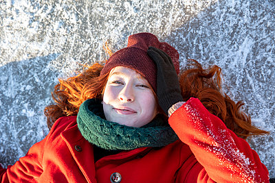 Beautiful woman wearing knit hat lying on ice - p300m2287639 by Frank van Delft