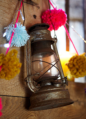 Rusty hurricane lantern and pompoms in wood cabin  UK - p349m2167850 by Sussie Bell