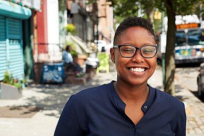 Black woman wearing eyeglasses smiling on city sidewalk - p555m1231803 by Granger Wootz