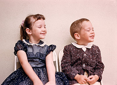 Caucasian brother and sister smiling with eyes closed - p555m1444175 by PBNJ Productions