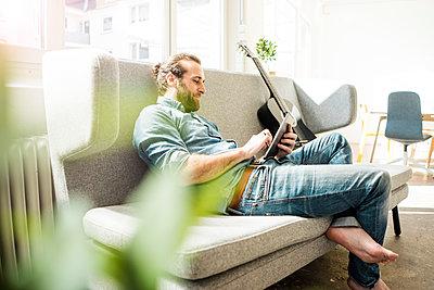 Junger Mann mit Tablet auf dem Sofa - p586m1511212 von Kniel Synnatzschke