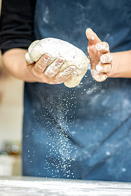 Baker kneading the dough - p879m2273316 by nico