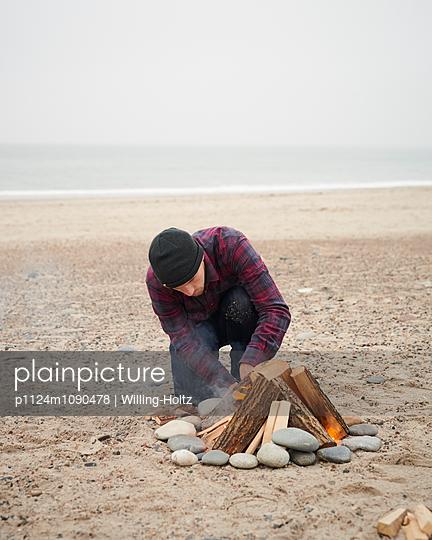 Mann zündet Lagerfeuer am Strand an - p1124m1090478 von Willing-Holtz