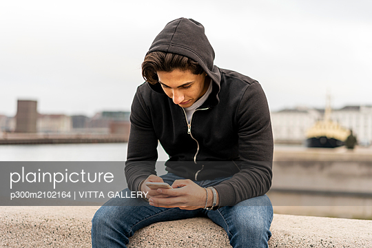 Denmark, Copenhagen, young man sitting on wall at the waterfront using cell phone - p300m2102164 by VITTA GALLERY