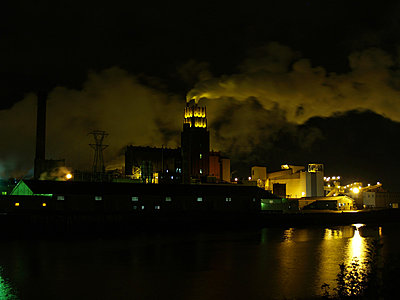 Dramatic night view of an industrial building illuminated against a smoky sky - p1072m828914 by Clive Branson