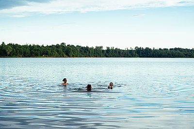 Female friends swimming in lake against sky at forest - p1166m2025274 by Cavan Images