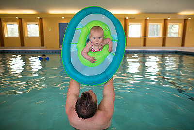 Happy baby girl playing with her father in swimming pool - p1166m2094984 by Cavan Images