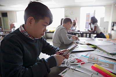 Boy middle school student working on science project in classroom - p1192m1473285 by Hero Images