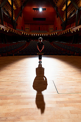 Shadow of female performer in spotlight on stage in auditorium - p1192m2123235 by Hero Images