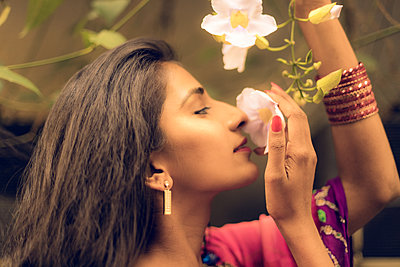 Beautiful Indian Woman smelling white flowers - p1417m2158386 by Jessica Lia