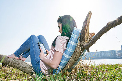 Young woman relaxing outdoors using tablet - p300m1449435 by Jo Kirchherr