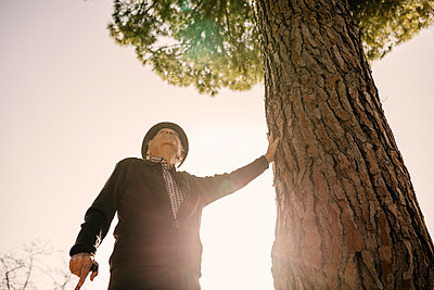 Spain, Barcelona. Senior man retired in a park with his cane and his hat leaning on a tree in winter - p300m2167183 von Josep Rovirosa