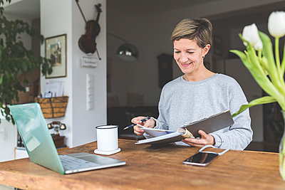 Mature woman working from home, using laptop on table with flowers - p300m2188140 by Anke Scheibe