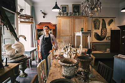 Portrait of smiling female owner standing in antique shop - p426m1114857f by Maskot