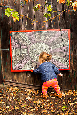 Caucasian baby girl drawing outdoors - p555m1306392 by Adam Hester
