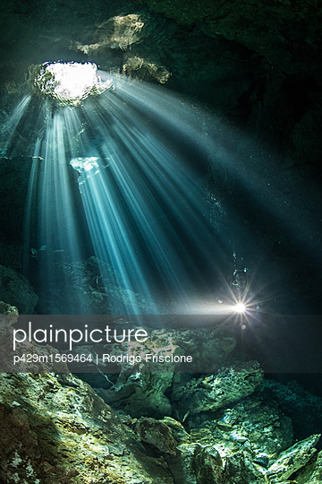 Male diver diving in underground river (cenote) with sun rays and rock formations, Tulum, Quintana Roo, Mexico - p429m1569464 by Rodrigo Friscione