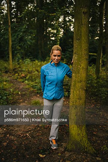 Junge Frau macht eine Dehnübung im Wald - p586m971650 von Kniel Synnatzschke