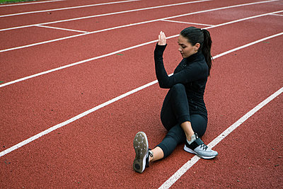 Young woman stretching on running track - p1520m2081887 by Michael Leckie