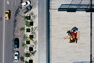 Aerial view of three people having a meal on the roof - p300m2131838 by Ekaterina Yakunina