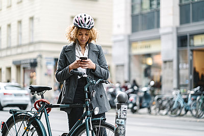 Woman with bicycle and smartphone in the city, Berlin, Germany - p300m2143493 by Hernandez and Sorokina