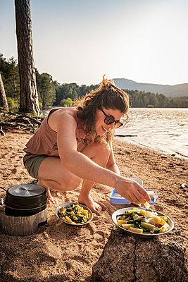 Woman garnishing pasta dish with parmesan, Reservoir de L'Ospedale, Corse-du-Sud, Corsica, France - p300m2144230 by Manuel Sulzer