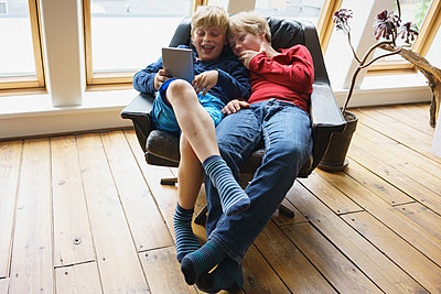 High angle view of happy brothers using digital tablet while resting on chair at home - p301m1180562 by Halfdark