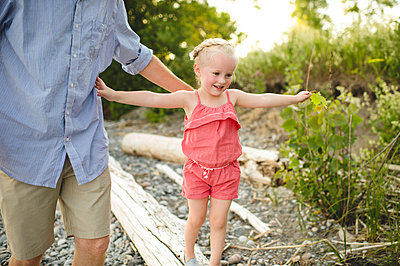 Girl with father stepping along tree trunk at Lake Ontario, Oshawa, Canada - p429m1174943 by Erin Lester