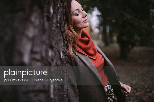 Portrait of woman with eyes closed leaning against tree trunk wearing turtleneck pullover - p300m2121726 by Oxana Guryanova