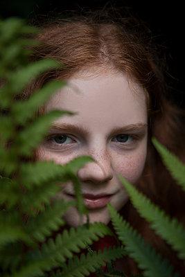 Mädchen blickt durch Farne - p045m1460766 von Jasmin Sander