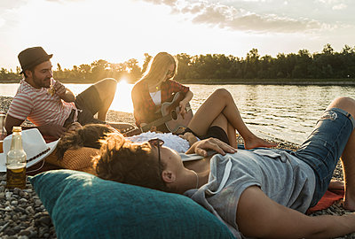 Friends relaxing at the riverside at sunset - p300m1188790 by Uwe Umstätter