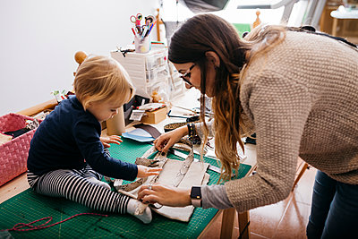 Mother with little daughter at home working with fashion accessories - p300m2058916 by Josep Rovirosa