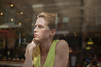 Thoughtful young businesswoman looking through window while sitting in cafe - p300m2220497 by LOUIS CHRISTIAN