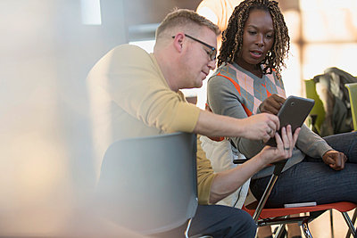 Coworkers looking concerned as they share a tablet computer. - p328m841022f by Hero Images