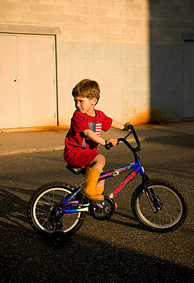 Young Boy Riding Bicycle With Training Wheels - p6943972 by Trevor Dixon