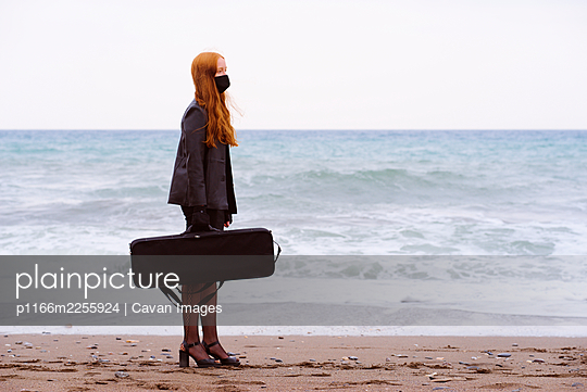 Young redhead woman with her bag next to the beach on a cloudy w - p1166m2255924 by Cavan Images