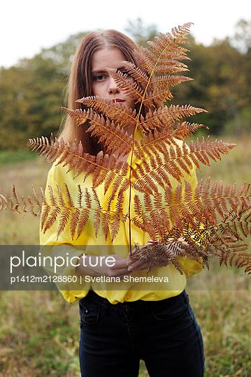 Teenage girl in yellow blouse holding fern in hand - p1412m2128860 by Svetlana Shemeleva