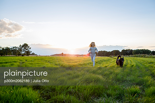 Girl with a dog running over a field at sunset - p300m2062189 by Julia Otto