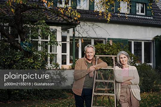 Portrait of senior couple with a ladder in garden of their home - p300m2155018 by Gustafsson
