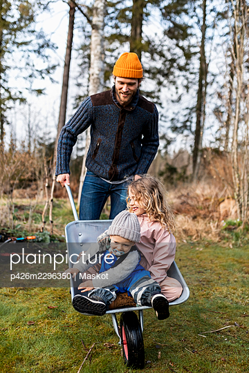 Playful man wheeling son and daughter sitting in wheelbarrow at back yard - p426m2296350 by Maskot