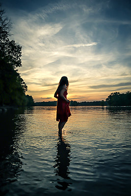 Sunset, Woman standing in river - p1019m2098797 by Stephen Carroll