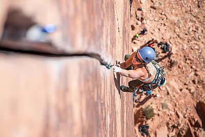 High angle view of female hiker wearing sunglasses while rock climbing - p1166m1555581 by Cavan Images