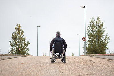 Rear vision of a disabled man in a wheelchair alone in the street - p1166m2146683 by Cavan Images