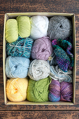 Colourful balls of wool in a yellow cardboard box, viewed from above. - p1433m2082656 by Wolf Kettler