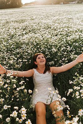 Girl in flower field - p1507m2168028 by Emma Grann