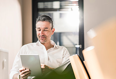Content businessman sitting in his office using tablet - p300m1449896 by Uwe Umstätter