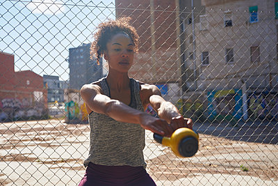 Spain, Catalonia, Barcelona, Dedicated young woman working out with a dumbbell - p300m2290706 von Pablo Calvo
